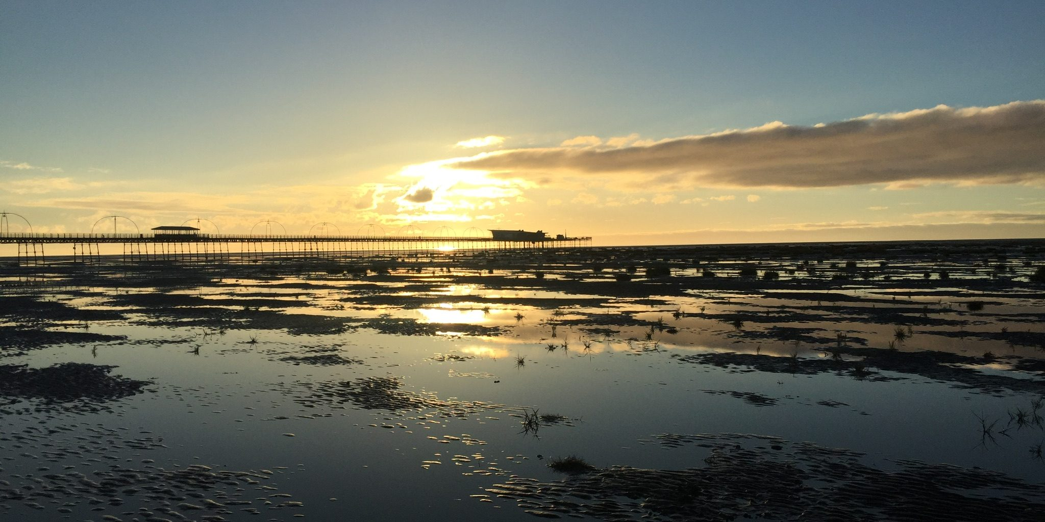 Sun going down over Southport Pier and Beach .